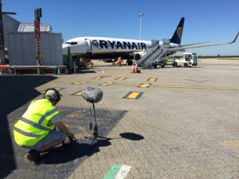 Photograph of Sound Recordist recording aeroplane at gate | Stansted Airport
