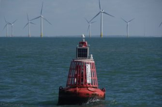 Close-up of buoy with wind farms in background