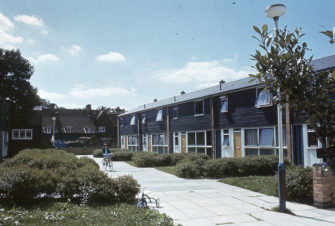 Colour photograph showing row of houses on right and green on left | JR James