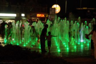 Water fountains illuminated with green light at night | The Dim Locator