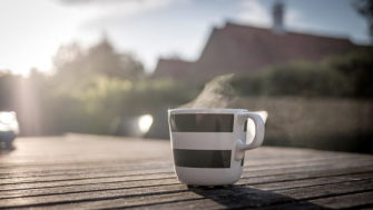 Close-up of coffee mug on table with blurred outdoor background | Pickpik.com